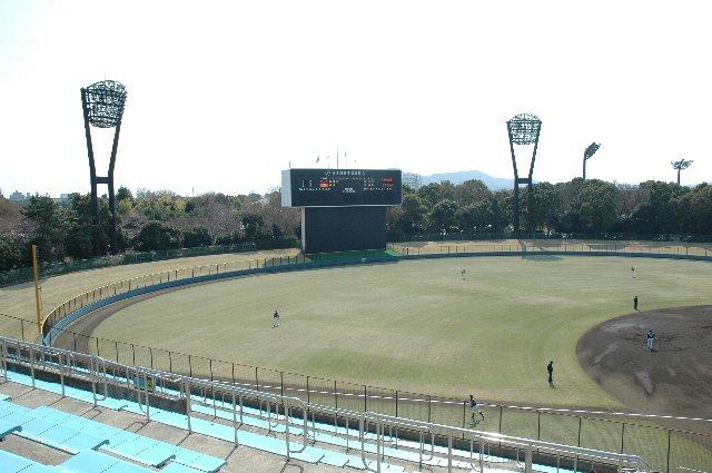 一塁側スタンドの奥に、サッカー場の照明を確認できる。