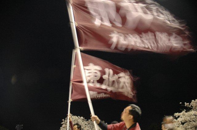 強風の中、応援団旗を支えて「東北魂」を見せる二人。
