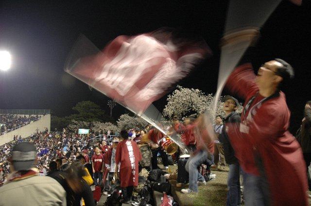 強風吹き荒れる中、力を込めて旗を振り抜き、観客が大注目。