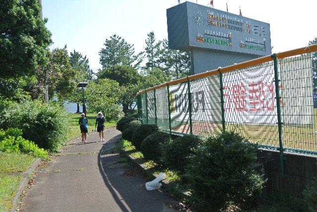 近くのグラウンドで練習中の中高生が通行中。