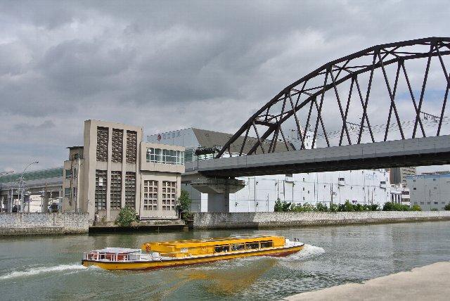 橋梁は阪神線の橋梁、運河をクルーズ船が通り過ぎている。