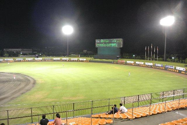 緑のフェンスに書かれたオレンジ色の広告がカクテル光線に映えます。