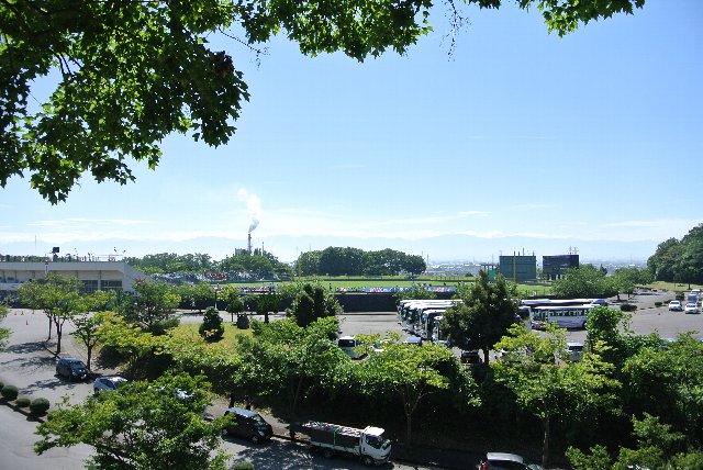 球場越しに高岡港周辺に広がる工業地帯が見えます。