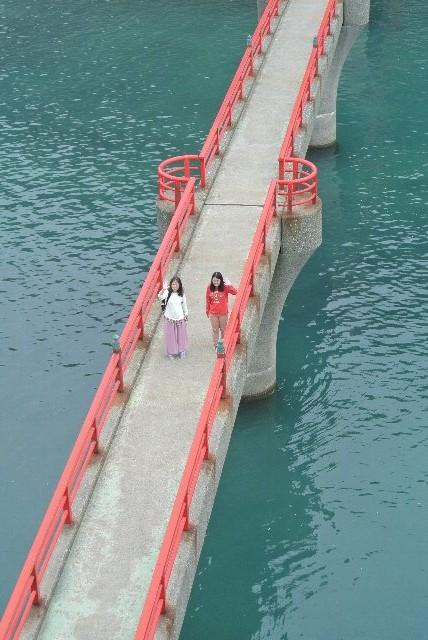 弁天岩の上から橋を渡る二人を狙う