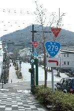 標識の奥に函館山が見える。