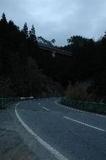 これから越える峠道が壁のように迫ってくる感じ、最高! 上の方にうっすら見えるのがこれから越える橋。