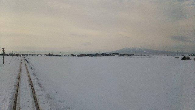 車窓に岩木山が大きく見えるのは金木まで、雪原が広がる場所を見つけて苦し紛れに撮った一枚。結構、上手く行った。